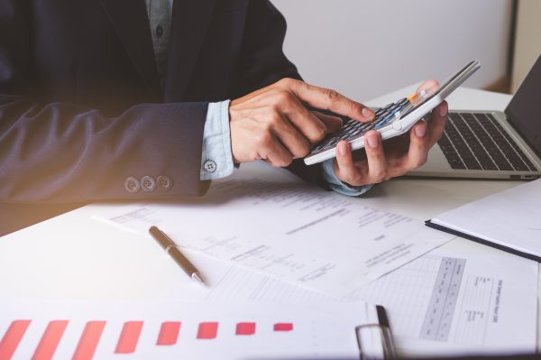 Close up view hands of businessman using calculator and doing accounting with graph and documents on the table.